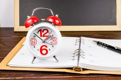 Alarm clock with notebook and black pen on wooden board Royalty Free Stock Photos