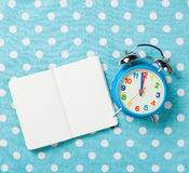 Alarm clock and notebook Stock Photography