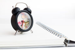 Alarm clock and notebook isolated on white Stock Photography