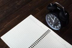 Alarm clock and notebook with pen on dark wooden floor, empty sp. Vintage alarm clock and notebook with pen on dark wooden floor, empty space for text Stock Photography