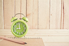 Alarm clock , notebook and pencil on wooden table Stock Images