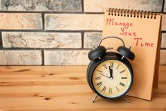 Alarm clock and notebook with phrase Manage your time on wooden table royalty free stock image