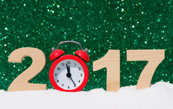 Alarm clock and the numbers 2017 in a snowdrift on a glitter background Royalty Free Stock Photo