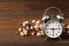 Alarm clock. Old windup loud alarm clock with a sprig of peach on wooden background Stock Images