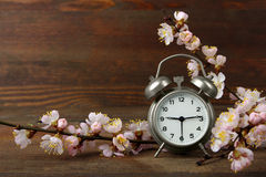 Alarm clock. Old windup loud alarm clock with a sprig of peach on wooden background Stock Photo