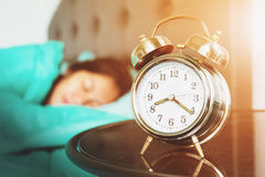 Alarm clock. Old alarm clock with woman sleeping on bed Royalty Free Stock Image