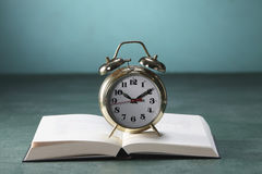 Alarm clock on open book Royalty Free Stock Photos
