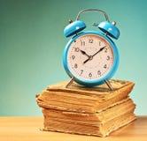 Alarm clock over the books Stock Image
