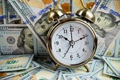 Alarm clock over money Stock Images
