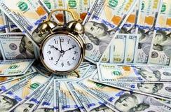 Alarm clock over money Royalty Free Stock Photos
