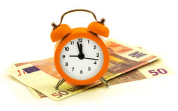 Alarm clock with paper money, 50 euro. Isolated on white background Stock Photo
