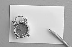 Alarm clock on paper Stock Photos