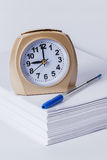 Alarm clock and pen on a stack of paper. On a white background Royalty Free Stock Photography