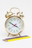 Alarm clock with pencils. Alarm clock with a pencil on a white background Stock Images