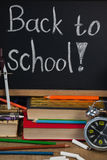 Alarm clock, pencils, chalk, books and slate with back to school text Stock Image