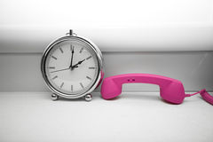 Old fashion clock and phone handset Royalty Free Stock Photography