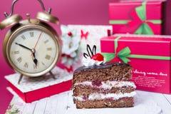 Alarm clock, piece of cake, present boxes Royalty Free Stock Photos