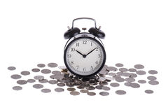 Alarm clock on a pile of coins  Royalty Free Stock Photos