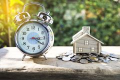 Modern alarm clock on a pile of coins and house placed stock photos