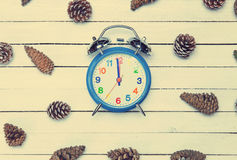 Alarm clock and pine cone. Spruce on a wooden table Royalty Free Stock Image