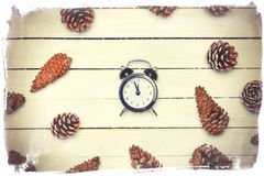Alarm clock and pine cone. Spruce on a wooden table Stock Photo