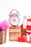 Alarm clock and pink body care accessories. Wooden sauna bucket, cabinet and a shelf of body care accessories isolated on white background Stock Photos
