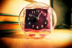 Front view of an alarm clock standing next to a pile of books on a wooden surface royalty free stock photos