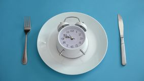 Alarm clock on plate, adhere to diet time, proper nutrition, discipline, closeup. Stock photo royalty free stock photo