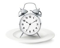 Alarm clock on plate isolated Stock Photos