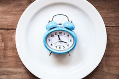Alarm clock in the plate. Time to eat. Business concept Royalty Free Stock Image