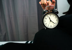 Alarm clock on pregnant woman belly Stock Photos