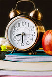 Alarm clock and red apple on top of a stack of workbooks, notebooks, pads. Pencils, pens, eraser on desktop. Black chalkboard Stock Image