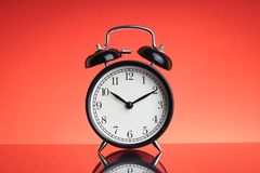 Alarm Clock on red background with selective focus and crop fragment. Business and Copy space concept royalty free stock photography