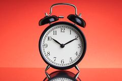 Alarm Clock on red background with selective focus and crop fragment. Business and Copy space concept stock image