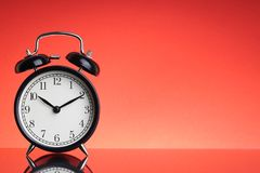 Alarm Clock on red background with selective focus and crop fragment. Business and Copy space concept stock images
