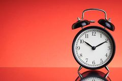 Alarm Clock on red background with selective focus and crop fragment. Business and Copy space concept stock photo