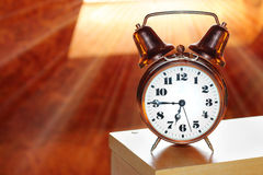 Alarm clock. Retro alarm clock in bedroom early morning. First sunrays in your bed, a new day begins Stock Image