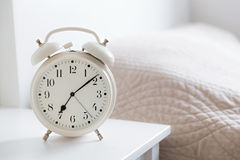 Alarm clock. Retro white alarm clock on white table in the bedroom Royalty Free Stock Photography