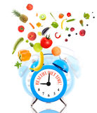 Alarm clock ringing and fruits with vegetables. Stock Photo