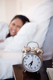 Alarm clock ringing next to woman in bed Stock Photography