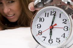 Alarm-clock rings. Irritated woman wakes up at 6 am because her alarm-clock rings stock photography