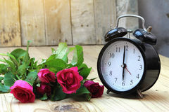 Alarm clock with roses on old wood royalty free stock photos