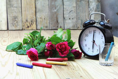 Alarm clock with roses on old wood stock photos