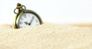 Alarm clock in sand. Old alarm clock in sand against white background 4k stock video