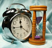 Alarm-clock and sandglass on b Royalty Free Stock Photo
