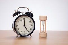 Alarm clock with sandglass standing on desk Royalty Free Stock Photo
