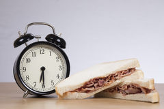 Alarm clock with sandwich on table Royalty Free Stock Photography