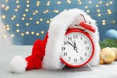 Alarm clock, Santa hat and festive decor on table. Christmas countdown royalty free stock photos