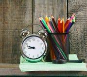 Alarm clock and school accessories . Stock Photos