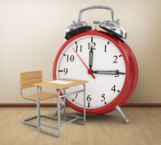 Alarm clock with school desk. Royalty Free Stock Photo